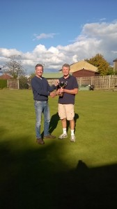 John presents David with the mens Janet Anderson single trophy.